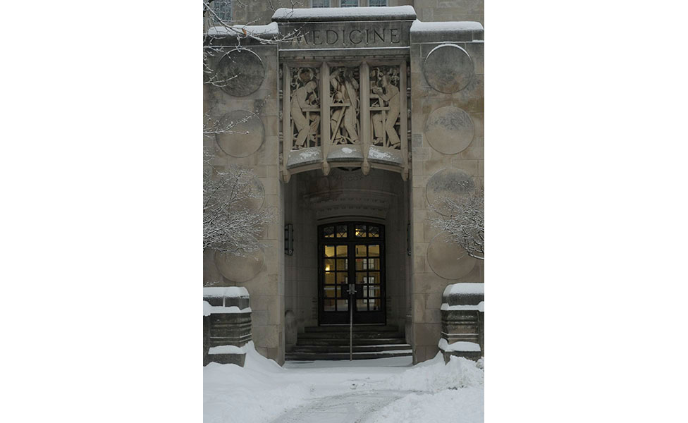 I've always loved the relief above the door at the former Indiana University School of Medicine building (now Myers Hall), and it looked so elegant framed in snow and with the warm light inside.   Photo by Ann Georgescu