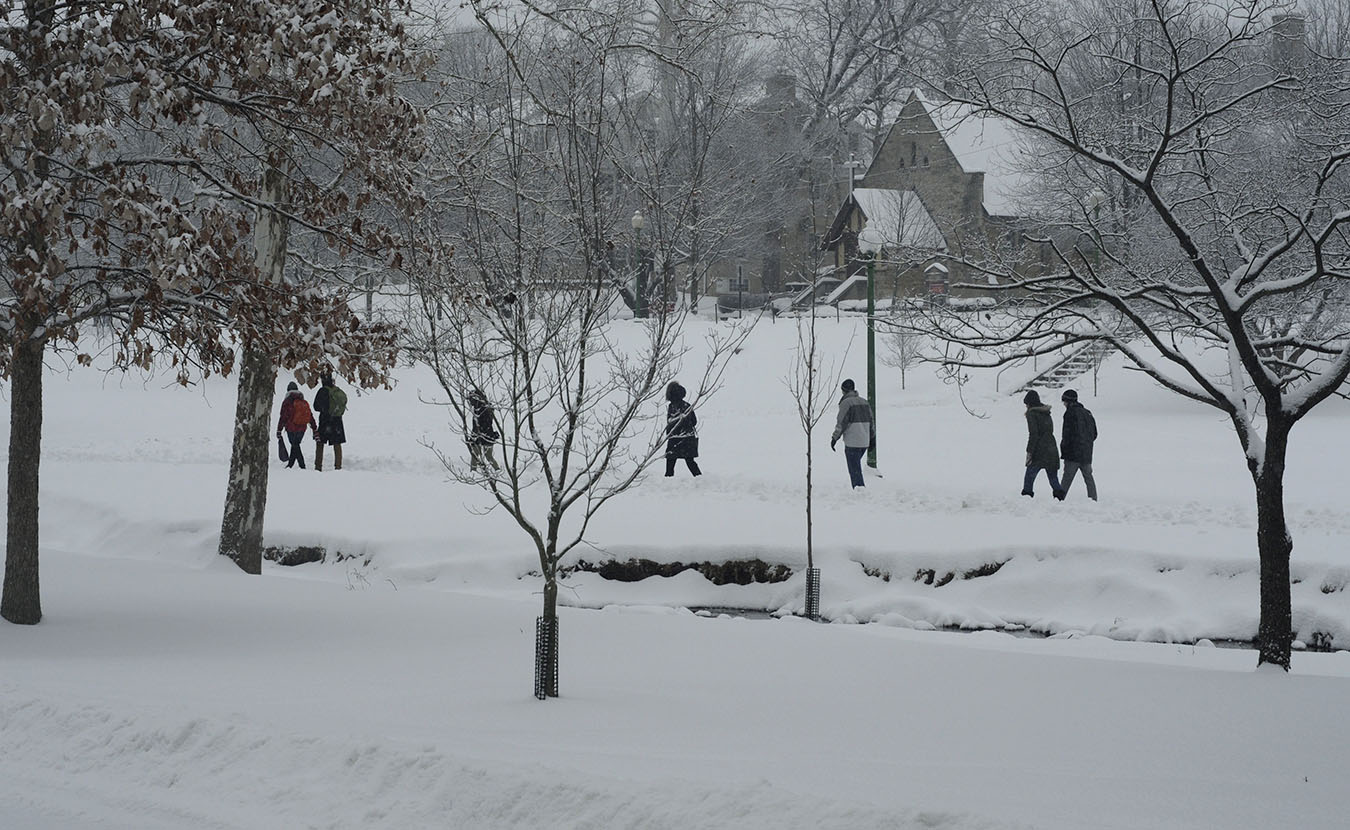 People walk, going along their business as usual despite the snow, through Dunn Meadow between Jordan River and East 7th Street.| Photo by Ann Georgescu