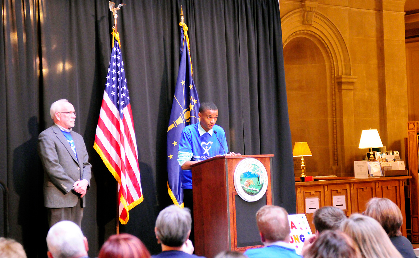 Dorian Phillips shares his experience in the Monroe County CASA program at the CASA Day rally at the Indiana Statehouse in March. His CASA of three years, Jim Shelton, stands with him in support. | Photo by Ann Georgescu