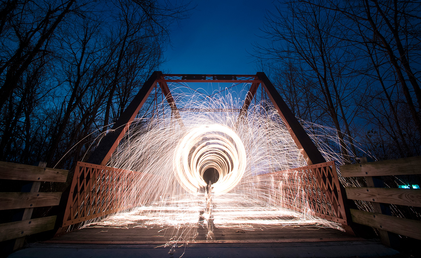 Nathan Clark spins steel wool on the Clear Creek Trail. Clark created this image by packing steel wool into a whisk, attaching it to a dog leash, lighting it on fire, and spinning it while using a long exposure. | Photo by Nathan Clark