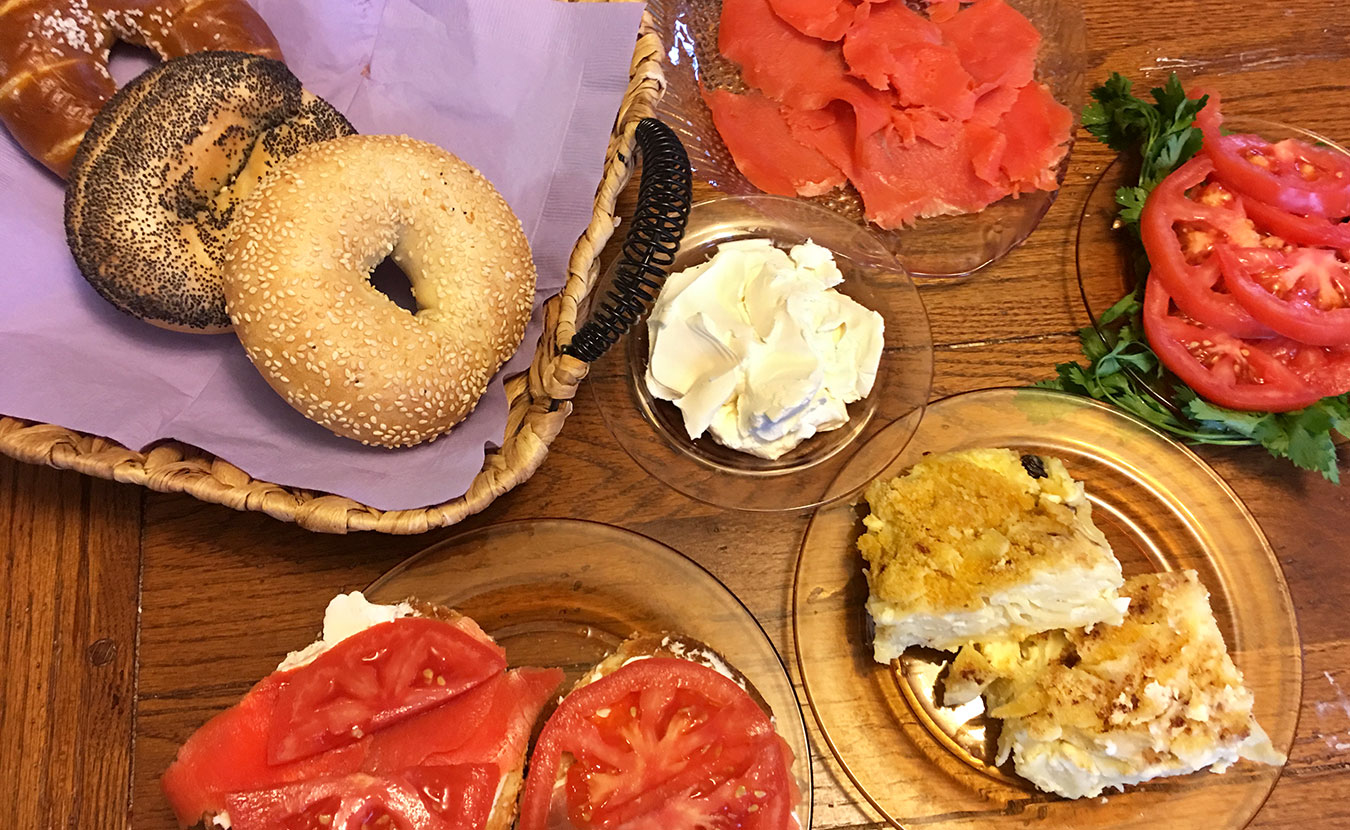 """Ruthie Cohen says Jewish soul food """"tastes like home."""" Foods pictured here include (clockwise from top left) bagels, cream cheese, lox, tomatoes, kugel, and a hearty sandwich.   Photo by Ruthie Cohen"""