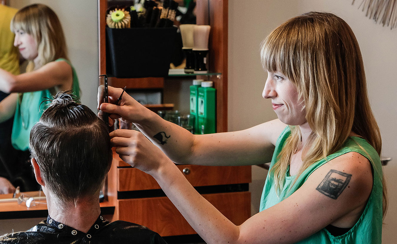 """Cathleen Paquet, a hairstylist at Hairstream Studio, styles a client's hair. She says this trade allows her """"to connect with other people really deeply."""" 