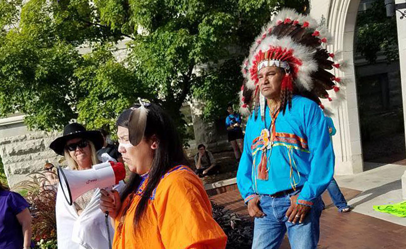 Writer Laura Reagan, wearing traditional Apache dress, speaks to a group of people at Sample Gates. As Halloween approaches, consider if your costume appropriates another's culture. | Courtesy photo