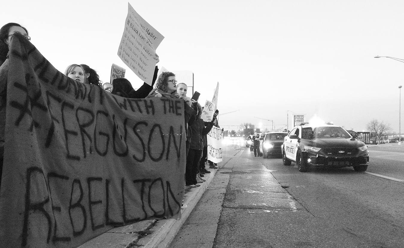 """How do people with similar values unite when their methods of action conflict with each other? Writer and organizer Alexandria Hollett says this question is illuminated by """"the difference between organizing campaigns on the one hand and symbolic activism on the other."""" Pictured here on the east side of Bloomington in 2014 is a Black Lives Matter protest, in solidarity with protesters in Ferguson, Missouri. 