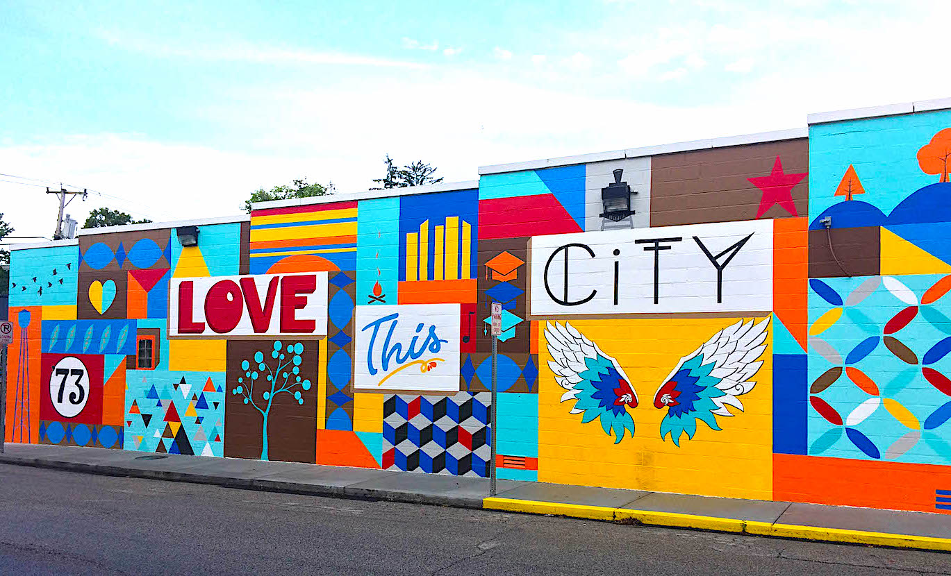 Photographer M.J. Bower photographed more than 30 murals in Bloomington to create a Bloomington Mural Trail. This mural, 'Love This City,' was painted by Eva Allen on the side of Mother Bear's Pizza's east-side location in spring 2019. The full list of murals is at the end of the article, as is a link to The Bloomington Trail Map. | Photo by M.J. Bower