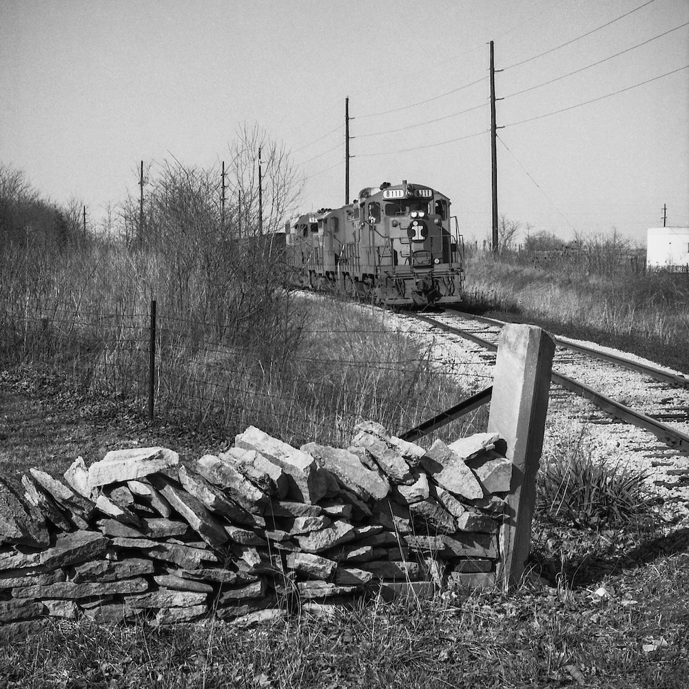 """This photo was taken by Limestone Post contributor Richard Koenig, the Genevieve U. Gilmore Professor of Art at Kalamazoo College in Michigan. Growing up in Bloomington, Richard often photographed trains throughout the area. Some of those photos became the focus of his essay """"Tracks Through Time: The Trains of 1970s Bloomington,"""" which is one of our most-viewed stories of all time. This southbound train is shown on its route between Morgantown and Bloomington, near Mt. Gilead Road and State Road 45 on March 25, 1977. Richard sent us this photo because of the limestone post in the foreground.   Photo by Richard Koenig"""
