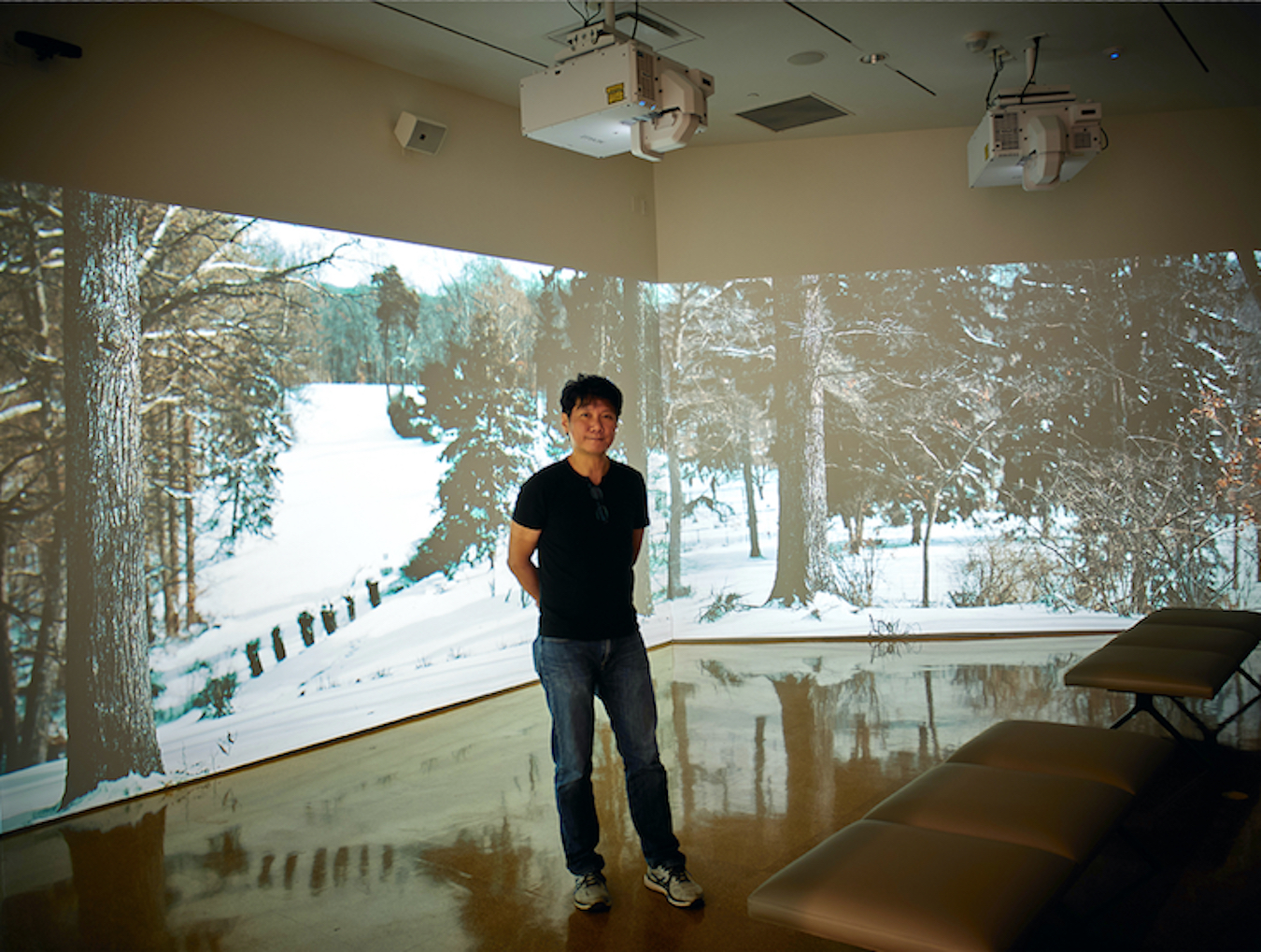 Photographer Paige Strobel visited several local galleries for her LP photo essay, 'Galleries Adapt to Pandemic While Artists Continue to Create.' Pictured is Jawshing Arthur Liou in front of his high-definition, multichannel video installation, 'House of the Singing Winds,' which shows the changing seasons at the historic home and studio of Hoosier painter T.C. Steele. The work is currently on view at the Sidney and Lois Eskenazi Museum of Art. | Photo by Paige Strobel