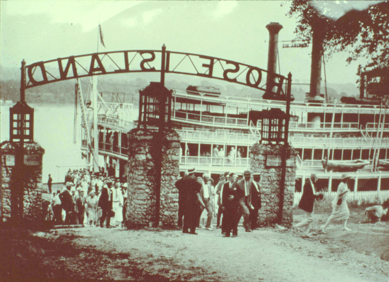 """Rose Island historical photo from the Jeffersonville Public Library/Clark County Visual History; the caption reads: 'The steamer, """"America,"""" is shown embarking passengers at the entrance to Rose Island around 1925. Notice how well dressed everyone is. The park was used by many church, school and club groups which made the gatherings a social event and not just a day in the park.'"""